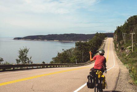 Un cycliste contemple la vue sur une route côtière