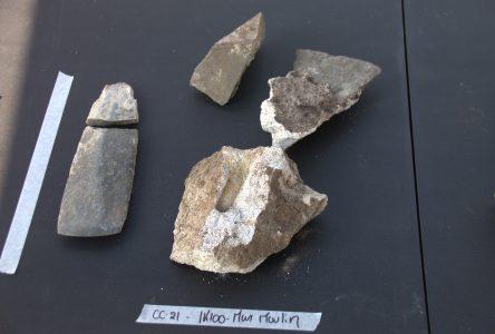 Les deux morceaux d'une hache de pierre et d'autres outils découvert sur le lieu des fouilles.
